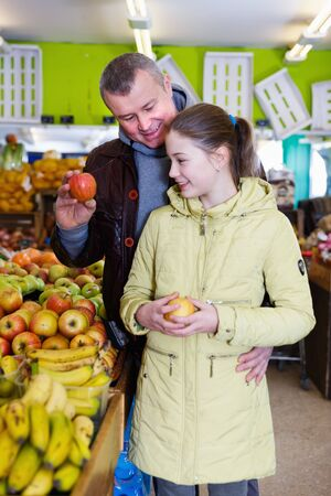 Portrait of father with daughter looking for ripe apples in fruit market Stock Photo