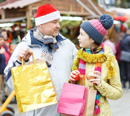 Portrait of smiling teen girl with her loving father holding shopping bags with purchases on street Christmas market Zdjęcie Seryjne