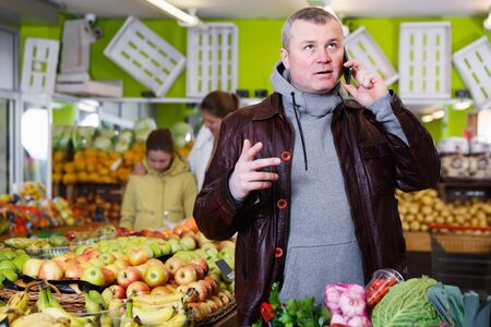 Smiling man solving questions by phone while buying fresh fruits and vegetables in store