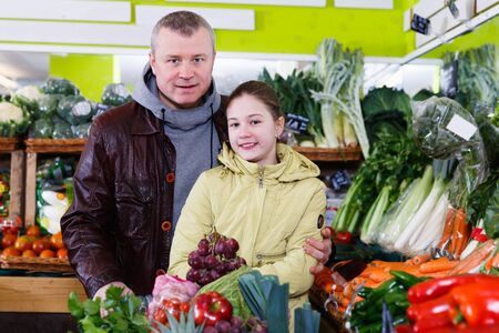 Portrait of young father with daughter choosing fruits and vegetables in market Stock Photo