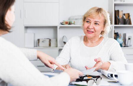 Reife Frau konsultiert einen Finanzberater für die ordnungsgemäße Durchführung der Hausbuchhaltung Standard-Bild