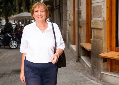 Smiling elegant middle aged woman walking along summer city streets Foto de archivo - 133745620