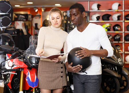 Glad shopping assistant helping   and demonstrating male customer motorcycles in store Stockfoto