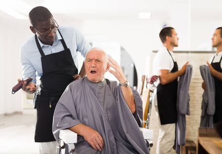 Portrait of upset dazed aged man sitting in barber chair with confused African hairdresser behind him Reklamní fotografie