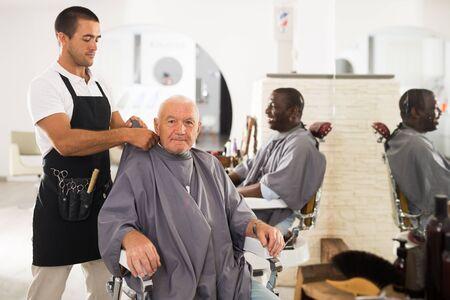 Portrait de jeune barbier amical mettant le manteau de coiffeur au client masculin âgé s'asseyant dans la chaise de coupe de cheveux dans le salon