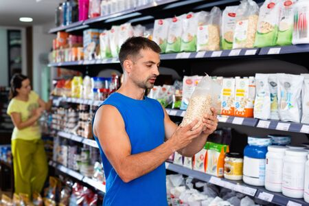 Focused glad cheerful muscular man looking for necessary sport nutrition products in shop, reading content label