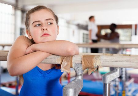 Portrait of sad  unhappy teenage girl in gymnastic swimsuit near sports equipment in gym