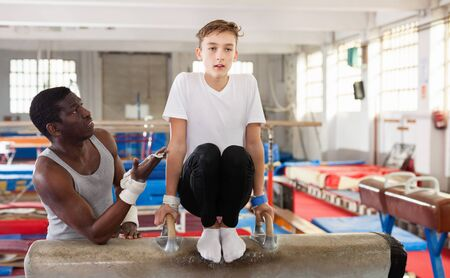 Efficient serious male coach training  positive teenage boy on gymnastic equipment at acrobatic hall