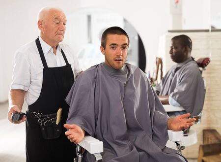 Young man unpleasantly surprised by haircut performed by elderly hairdresser at barber shop Reklamní fotografie