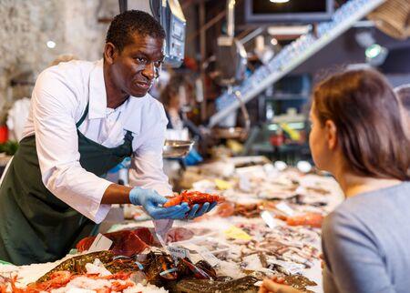Positive male African American seller serving customer fresh shrimps at seafood market