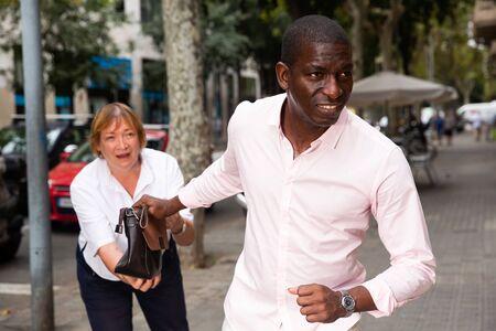 Concept of street theft. African man snatching bag of frightened elderly woman on city street Foto de archivo - 133745653