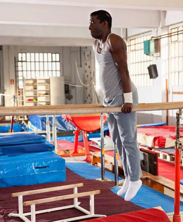 Portrait of glad positive man in sportswear doing exercises on parallel bars at gymnastic hall