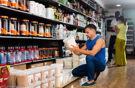 Focused  cheerful  smiling muscular man looking for necessary sport nutrition products in shop, reading content label Stock Photo