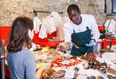 Friendly man seller serving customer raw fish at seafood market