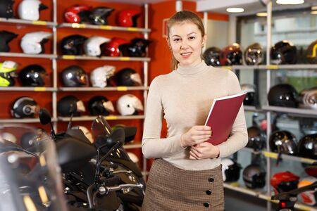 Pretty female seller holding advertising brochure in modern motorcycle salon Stockfoto