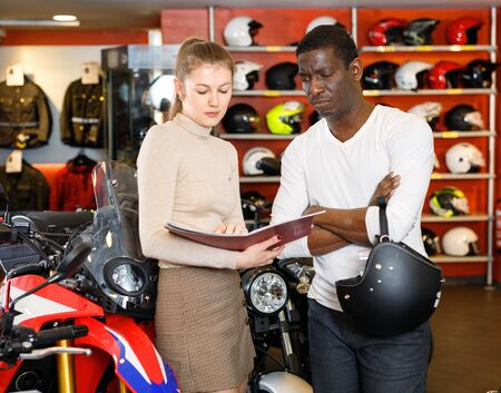 Polite  diligent  cheerful female seller communicating with male customer in modern motorcycle salon