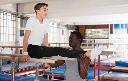 African male coach helping teenage boy doing gymnastic exercises on equipment