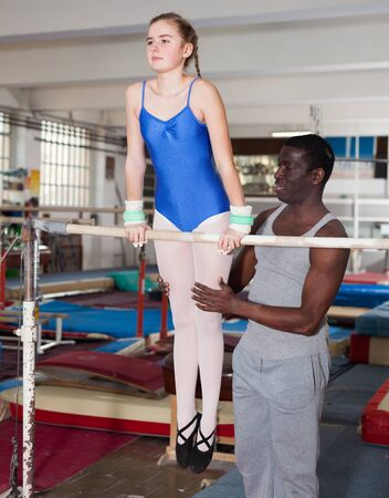 African male coach training teenage girl on gymnastic equipment at acrobatic hall