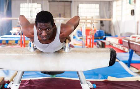 portrait of adult afro man in sportswear doing exercises on pommel horse in acrobatic hall