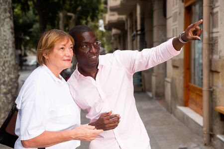 Polite African American man pointing direction to elderly female tourist on summer city street