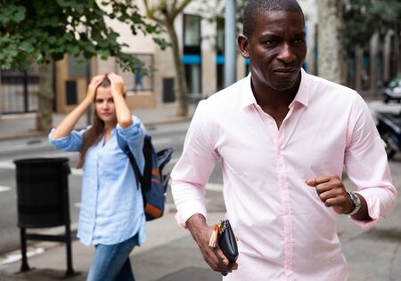 African guy holding stolen wallet running away from young female tourist strolling around city. Street theft concept