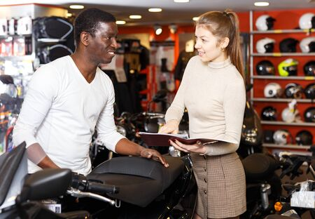 Positive female seller helping man to choose new motorcycle and riding gear in shop Фото со стока