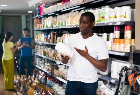 Interested athletically built African man choosing for sports nutrition, reading label carefully before buying in shop