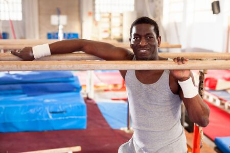 Portrait of glad  man in sportswear doing exercises on parallel bars at gymnastic hall