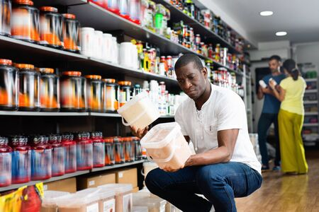 Focused  glad muscular African man choosing sports nutrition products in shop, reading content label