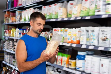 Man looking for sports nutrition before buying in shop Stock Photo