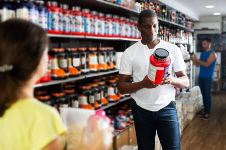 sportive young athletic African looking for necessary food supplements in sport nutrition store