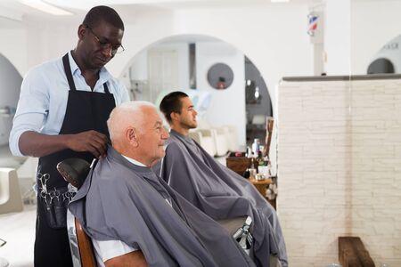 Un coiffeur afro-américain habile mettant une cape de coiffeur à un client masculin âgé assis dans une chaise de coupe de cheveux