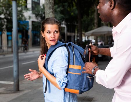 Street thief stealing wallet from backpack of young woman walking through city