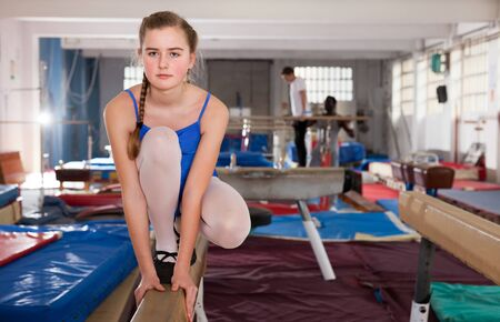 Positive teenage girl in gymnastic swimsuit training gymnastics at gym