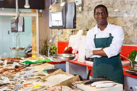 Smiling male fish shop worker in apron near showcase with raw seafood