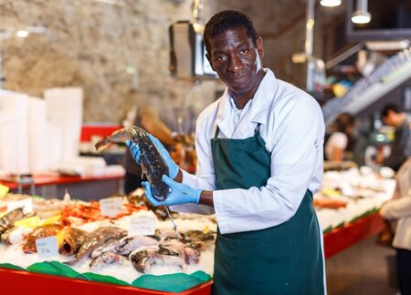 Positive seller in apron standing near counter offering fresh fish