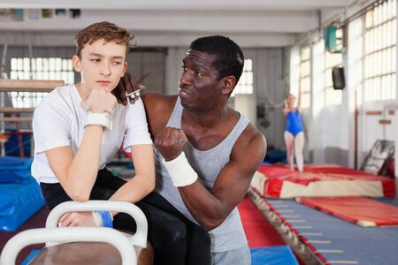 Efficient serious male coach talking with teenage boy on gymnastic equipment at acrobatic center