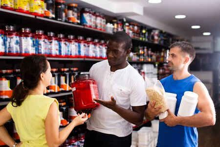 Interested athletic people holding plastic jars with sports supplements discussing in store interior