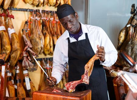 Confident African American salesman cutting delicious ham for sale in butcher shop