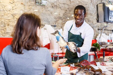 Portrait of salesman in apron offering female customer fresh fish at seafood shop