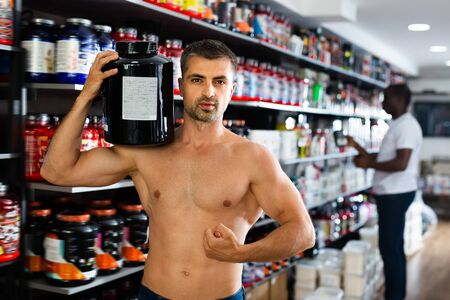 Happy bare to waist man showing muscles while standing in store of sports nutritional supplements