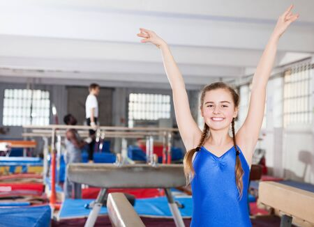 glad teenage girl rejoicing at her sporting success at gymnastic hall Stockfoto
