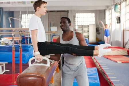 young afro trainer helping teenage athlete with exercise technique at acrobatic hall