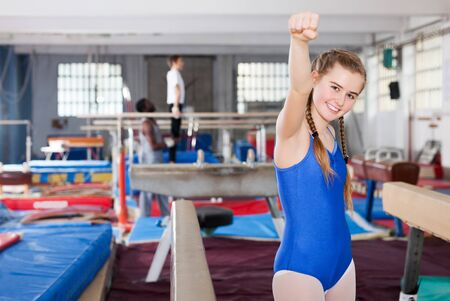 smiling teenage girl rejoicing at her sporting success at gymnastic hall