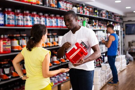 Confident athletically built African male recommending sports supplements to female client at sports nutrition store