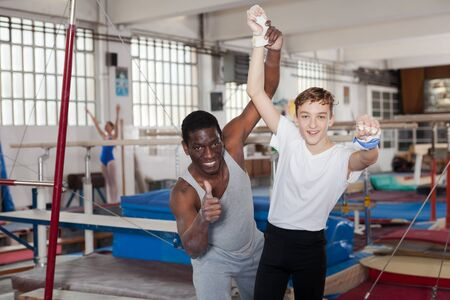 Male coach trainer and teenage athlete exulting sporting achievements at acrobatic hall