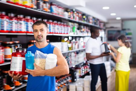 Adult muscular man with jars of sports nutritional supplements in store