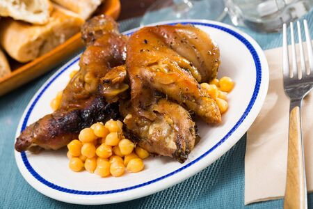 Baked spicy pig trotters served with garbanzos on white plate Stockfoto