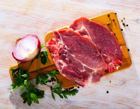 Sliced raw pork chop with parsley and onion