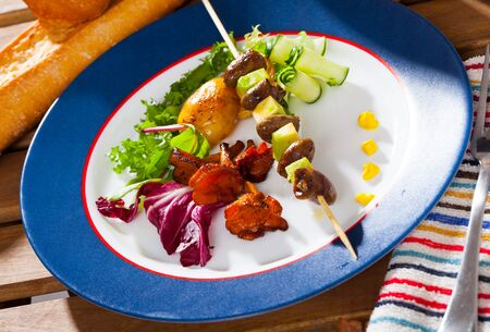 Grilled chicken hearts with avocado on skewers served with vegetables and fried chanterelles on blue plate